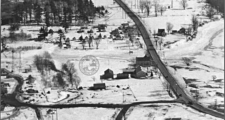MAPLE GROVE AT ROBERTSON CREEK Looking east, the French-Robertson house, first house on the left, northside of hwy #2. Beyond is the frozen Robertson Creek and summer cabins.  At the very top right hand corner one can just make out the tombstones in the Maple Grove cemetery.  The roads at the bottom of the photo lead to a construction camp.